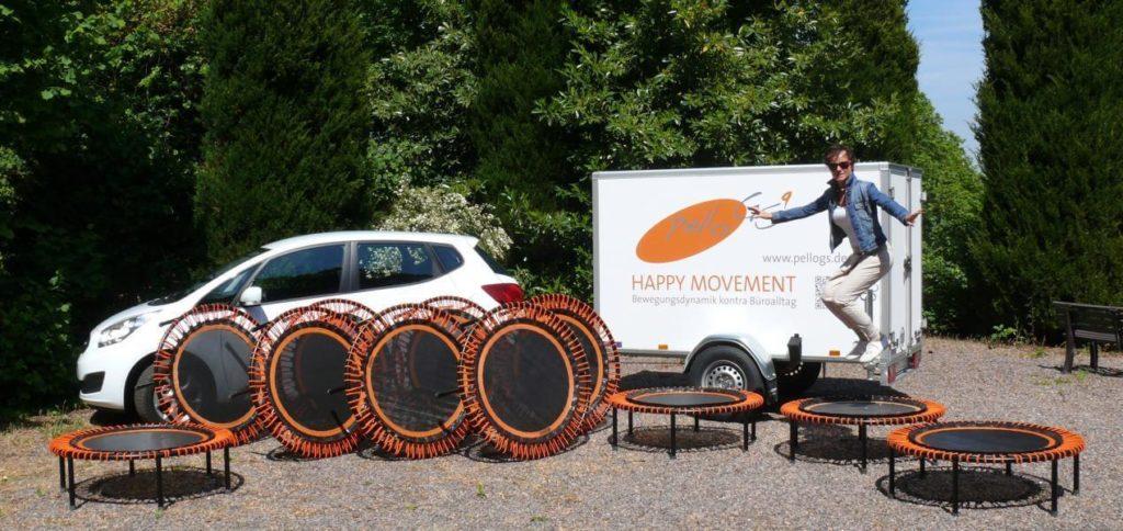 """Das pelloGS Mobil. Weißes Auto mit dem pelloGS Logo und der Aufschrift """"Happy Movement"""". Trampoline der Marke bellicon sind aufgebaut."""